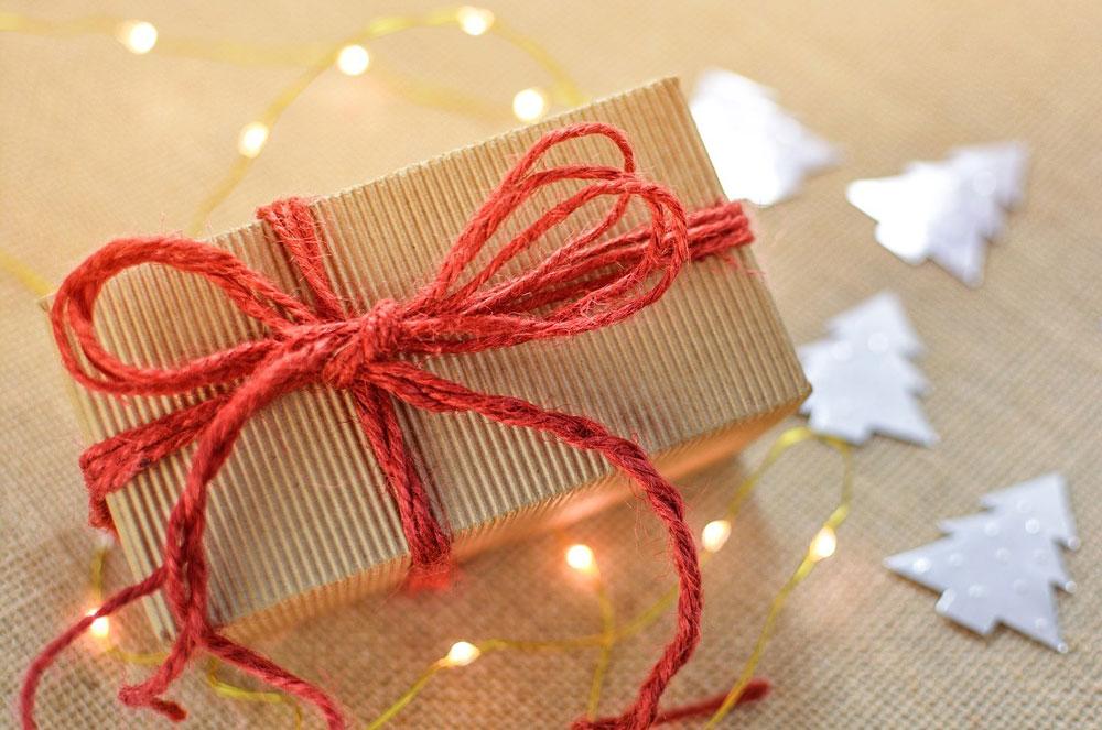 Eine Geschenk-Box, die mit einem roten Band verschnürt ist.